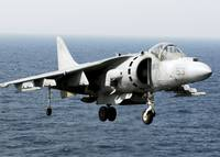 An AV-8B Harrier hovers over the flight deck of US