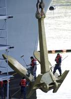 Sailors paint the starboard anchor of the aircraft