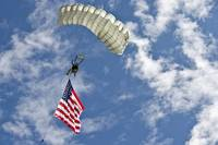 A U.S. Air Force member glides through the sky wit
