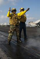 Airmen direct an F/A-18C Hornet on the flight deck