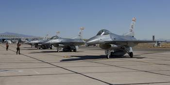 F-16s line up at the end of the runway for preflig