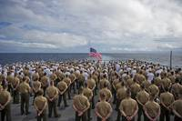 Marines and sailors stand in formation during a ce
