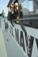 US Navy Boatswains Mate looks through binoculars a