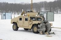 U.S. soldiers take cover behind a humvee during Co