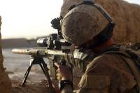 U.S. Marine looks through the scope of his M16A4 r