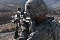 U.S. Army sniper scans a village in Afghanistan fo