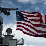 """USS Cowpens flies a large American flag during a l"" by stocktrekimages"