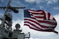USS Cowpens flies a large American flag during a l