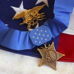 """The Medal of Honor rests on a flag beside a SEAL t"" by stocktrekimages"