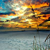 Fiery Burning Red Clouds Sunset Foot Prints Beach Art Prints & Posters by eszra tanner