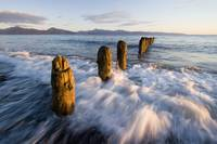 Surf rushing around old pilings along beach Homer