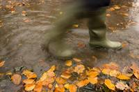 Person In Motion Walks Through Puddle Filled With
