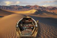 Drift boat resting on sand dunes in Death Valley N