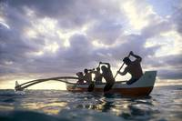 Hawaii, Men On Outrigger Canoe Paddle Into Sunset