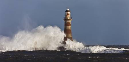 Waves Crashing Against A Lighthouse Sunderland, T
