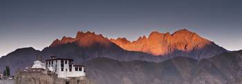 A Building On A Rock Ledge With Alpenglow Over The