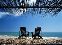 Two Chairs On Deck By Ocean Shaded By Grass Roof