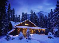 Snow Covered Cabin With Christmas Lights In the Mo