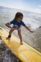 A young girl on a yellow surfboard, Gold Coast, Qu
