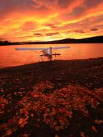 A Float Plane Facing The Sunrise Over Teslin Lake,