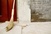 China, Beijing, A Broom Leaning Against A Cement W