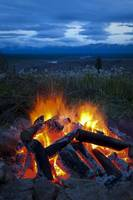 Close up view of a camp fire with a view of the Ch