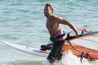 Man Comes Walks In The Water With Windsurfing Equi