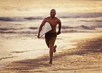 A Man Runs On The Wet Beach At Sunset With Surfboa