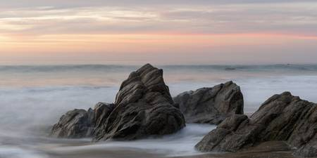Mist Surrounding Rocks In The Ocean At The Coast A