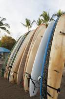 Surfboards Standing Up Against A Rack On The Beach