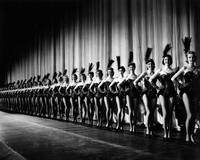 Rockettes in tight line in front of curtain