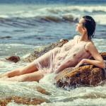 """woman on rock in beach"" by andriy_petrenko"