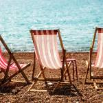 """Stripy Deckchairs Pebble Beach Sea and Sunshine"" by NatalieKinnear"