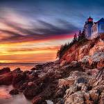 """Lighthouse on a Cliff at Sunset"" by George_Oze"