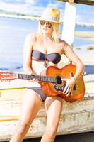Young Attractive Blonde Woman Playing Guitar