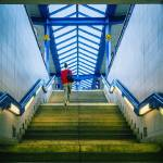 """Woman climbing staircase to railway platform"" by ingojez"