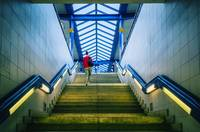 Woman climbing staircase to railway platform
