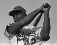Jackie Robinson swinging a bat in Dodgers uniform,