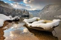 Snow covered boat on Lake Bohinj in Winter