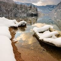 Snow covered boat on Lake Bohinj in Winter Art Prints & Posters by Ian Middleton