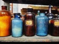 Orange, Brown and Blue Bottles of Chemicals