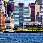 """Tugboat Pushing Barge Near Manhattan Skyline"" by susansartgallery"