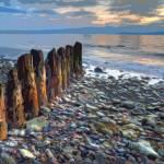 """Worn Pilings on Rocky Shoreline"" by ElainePlesser"