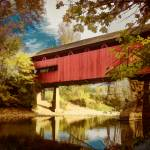 """Red Covered Bridge Over Stream in Autumn"" by ElainePlesser"