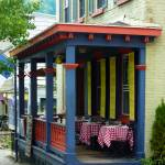 """Outdoor Cafe with Checkered Tablecloths"" by susansartgallery"