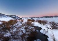 River Flowing in snow field sunset