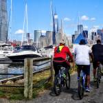 """Three Bicyclists By Liberty Landing Marina"" by susansartgallery"