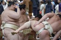 Sumo Wrestlers Stretching Before a Tournament