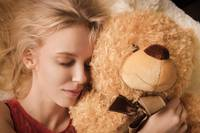 girl lying with teddy bear