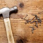 """Hammer & pile of rivets, nails on wood background"" by Mohamed-Fadly"